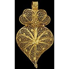 Delicate Portuguese Pendant ~ The shape of this gold filigree pendant is typical of northern Portugal. Similar pendants were also made in sheet gold, with engraved or applied filigree decoration, but always in the same shape of a heart with a curved point, and crown-shaped top. In the 16th century traders carried Spanish and Portuguese fashions in jewellery around the world. Heart-shaped brooches, like this pendant, are still worn today in Malaysia.
