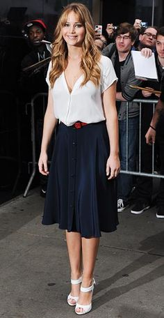 Jennifer Lawrence in a simple Joie shirt and a full navy skirt from Holmes & Yang with a red belt and white sandals