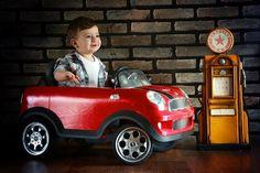Lucca aparece na foto com seu carro vermelho no estúdio. A criança foi clicada ao lado de um bomba de gasolina para representar o motorista da série de fotos com bebês caracterizados como diferentes profissionais