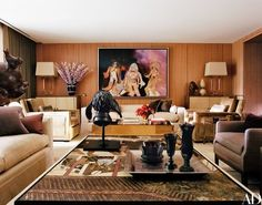 In the television room, a painting by Richard Prince hangs above a custom-made sofa by Jonas and a brass Gabriella Crespi low table from Nilufar. The oak-and-parchment cabinets are by Paul Dupré-Lafon. Floral design by Ariel Dearie Flowers | archdigest.com