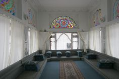 An Arabic style majlis (sitting room) with cushioned floor sofas & stained glass windows.