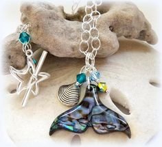 This Whale Tail necklace is a great addition to your Summer accessories.A Paua pendant shaped like a whale tail or dolphin fin is the focal point of this necklace.Paua shell is a natural shell product and native to New Zealand. It has a beautiful marbled iridescent background and has a similar look to Abalone shell.Dangling with the Paua pendant are 5mm Swarovski Bicone crystals in Indicolite, Aquamarine and Jet AB2x along with a silver-toned metal shell bead. #zibbet