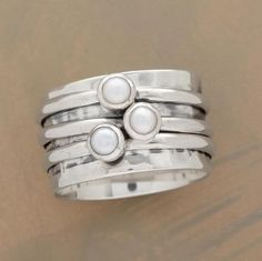 "Three spinning rings with orbiting cultured pearls on a hammered base band. Exclusive. Handcrafted in sterling silver. Whole sizes 5 to 9. 7/16""W."