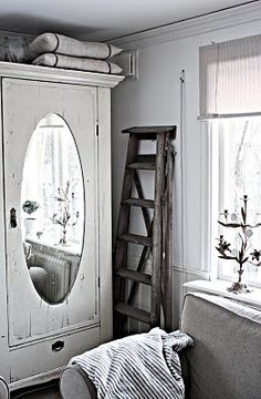 mirrored armoire creates illusion of more space, old ladder is charming