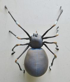 Soft Sculpture of a spider. Made from Taffeta and thick wire legs covered in floral, tissue and crepe papers. Designed as a decorative object she