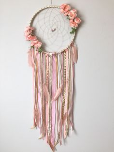 This dreamcatcher is so feminine and gorgeous!! Boho chic adorned with peachy pink silk flowers on both sides of the web, beautiful specialty beads, pink, peach & gold fabric & extensions, and peachy feathers. The base is wrapped in cream/gold fabric with a cream twine hand woven web, holding 2 flower specialty beads. This dreamcatcher has a soft and beautiful look that would be perfect for any room and especially a baby girl or any age girls room! Specific flowers may vary due ...