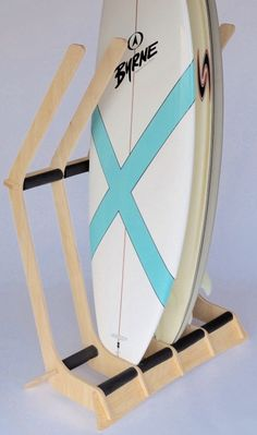 A wooden, freestanding surfboard floor rack that stores 4 surfboard vertically