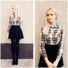 red, green, and white plaid button down. black pleated skirt. black tights. black shoes.