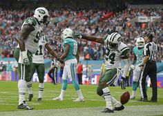 NFL Week 4 live box scores and udpates -   New York Jets' Darrelle Revis, right, celebrates after making an interception over Miami Dolphins' Jarvis Landry during the NFL football game between the New York Jets and the Miami Dolphins and at Wembley stadium in London, Sunday, Oct. 4, 2015. (AP Photo/Matt Dunham)