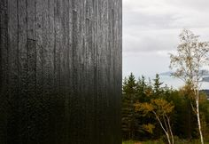 Canadian studio Alain Carle Architecte has embedded a black, sculptural dwellinginto a sloped site overlooking the St Lawrence River. Called La Charbonnière, the home is part of a housing development on a mountainside in Cap à L'Aigle, a resort village in Quebec's Charlevoix region. The site had been cleared by the developer to provide views