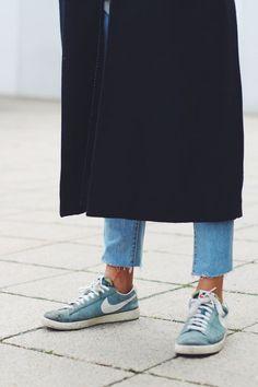 black coat, raw hem jeans & all worn Nike sneakers
