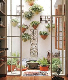 """""""Este jardim é ideal para áreas em que  piso seja cimentado, pois o mesmo é encoberto pelos seixos e as espécies plantadas em vasos dispostos na parede e piso"""""""