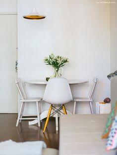 Sala de jantar com mesa e cadeiras brancas e pendente com parte interior dourada.