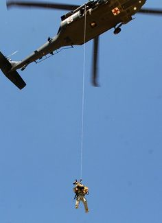 """Staff Sgt. Michael Hile with """"Rronnie"""", his military working dog, 554th Military Police company is being hoisted into a UH-60 (Blackhawk) helicopter during a canine-hoist training mission July 15 near Bagram Airfield, Afghanistan. (US Army photo by Spc. Aubree Rundle)"""