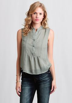 This ultra-soft sage green blouse features a subtle woven plaid design with a front button placket.