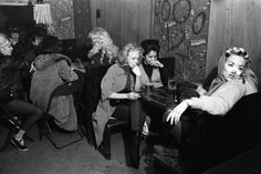 "In one of the most extraordinary unpublished photographs Bill Ray made while with the Hells Angels in 1965, a group of women -- including one with what appears to be a bandaged, broken nose -- hang out in a bar while the bikers gather in a separate room. ""The men were having a business meeting,"" Ray remembers, ""and the women were definitely not invited there. When those guys were busy, the women just sat and waited. They'd smoke, drink beer, gossip..."""