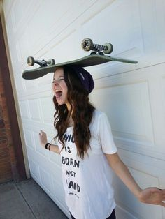 スケートボードを頭にのせる女性