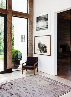 A vintage Chinese rug and a Danish chair Kayne's husband owned when they first met are simple comforts warming up the expansive foyer. Photos by Nicole Lamotte via One Kings Lane - Amazing Interior Design Design Entrée, Home Design, Decoration Inspiration, Interior Design Inspiration, Decor Ideas, Style At Home, Home Pictures, Interior Exterior, Home Interior