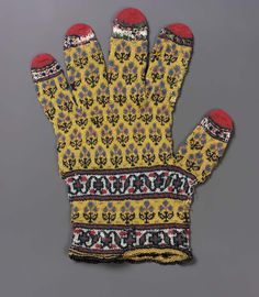 """19 c. probably. Glove. Indian. Very fine wool. Knitted. Dimensions: 18.5 cm (7 5/16 in.). Accession Number 30.12 Glove """"from the stores of Nizam of Hyderabad."""" Material: very fine wool. Design: rows of small conventional blue flowers, ends of fingers crossed by bands of white and tipped with red, two white bands with red and green vine around wrist: worn andmended."""