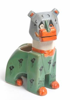 """Louis Wain"" ""Haw Haw"" Futurist Cat, design registered 1914, modelled seated smoking a pipe, painted green, black, grey, orange and brown, printed and painted marks including trident mark, Made in England, Rd No 638312 and the body with painted mark Louis Wain, 13.5cm (crazed)."