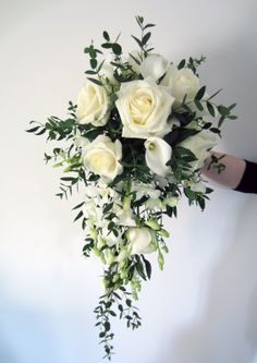 "dendrobium white orchids - roses, calla lily and for the greens, it looks like Italian ruscus. I would use different greens on the top and sides and add variegated ivy as the long stems along with the ruscus. This is a tear drop and by adding different greens, it would be less formal and would have more ""movement"" and texture."
