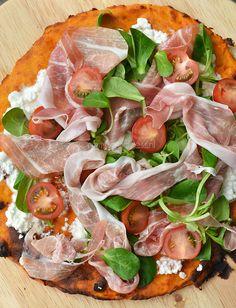 Zoete aardappelpizza. Ingrediënten: Pizzabodem: • 400 gram zoete aardappel • 70 gram patent bloem • 1 ei • peper en zout Toppings: • Hüttenkäse • Veldsla • Parmaham • Cherrytomaatjes