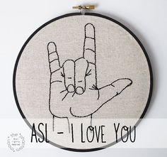 I Love You is exactly what this hoop says in Sign Language. How awesome is that? And bonus, only you and your other cool signing friends will know what this baby says. Aw yeah.   DETAILS + DISPLAY OPTIONS ✫ This hoop has been 100% hand sewn using natural linen fabric, thread and a lot of love. ✫ Stretched over a hand painted 7 inch wooden hoop, this sweet piece of embroidery is ready to be displayed and can either be hung or stand alone on a shelf.   OTHER SIGN LANGUAGE / ASL TREASURES ...