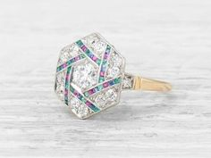 Vintage Art Deco ring set with an old European-cut diamond weighing approximately 0.40 carat. within an hexagonal setting of calibré-cut sapphires, rubies, and emeralds and 12 additional single-cut diamonds. Set in platinum and gold. Circa 1925 One of our most unique and rare settings. The hexagonal shape and alternately-set sapphires, rubies and emeralds make this an extra special example of Art Deco design. Learn more about Art Deco rings Diamond and gold mining has caused devastation in…