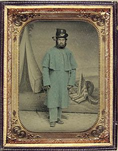 Wonderful picture of Civil War soldier of the Union army standing in front of painted backdrop representing a military encampment.