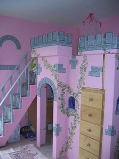 A pink princess castle loft bed. Built from MDF with 3 bookshelves around the bed. There is room underneath to use as a playhouse. Carpeted staircase up to the bed. Windows on front and on one side.
