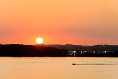 A motorboat crosses Lake Mendota as a fiery sun sets over Picnic Point at the University of Wisconsin-Madison during summer on June 30, 2012.