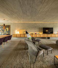Casa, decoração de casa, modernismo. Correr de madeira e cinza com luz natural. Parede cinza, poltrona, quadros, banco de madeira e luz natural.