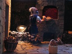 the baker removes bread from the oven in the castle kitchen.  my work - our miniatures group made a castle as a joint project, we each produced a room box depicting one of the rooms.  This was my Castle Kitchen, I also made the food and the figures. #scaleminiatures #miniatures #112ScaleMiniature