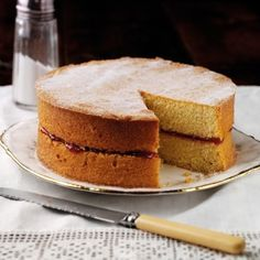 Victoria sponge cake dusted with sugar with one slice removed.