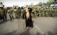 Chinese riot police watch a Muslim ethnic Uighur woman protest in Urumqi in China's far west Xinjiang province on July 7, 2009 following a third day of unrest. Police fired tear gas to disperse thousands of Han Chinese protesters armed with makeshift weapons and vowing revenge, as chaos gripped this flash-point city riven by ethnic tensions following rioting that claimed at least 156 lives. Authorities ordered a night curfew and thousands of heavily armed police deployed across Urumqi