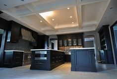 Contemporary ebony kitchen design with black kitchen cabinets, slate blue glass tiles backsplash, coffered ceiling, white quartz counter tops, double ebony kitchen islands and La Cornue Range.