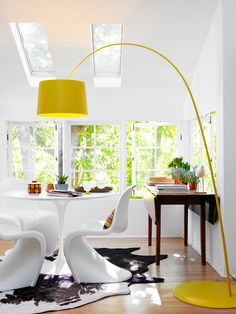 Ashe + Leandro - Kitchen nook with oversized yellow light, antique drop leaf console, tulip table