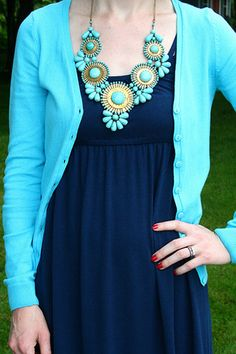 I love the light blue sweater against the dark blue dress. Not loving the necklace though.