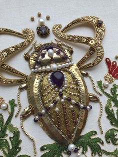 My new work. Louis the Jewel Beetle. With my sincere gratitude to Hanna Karlzon who gave her permission to use her drawing as a pattern for my embroidery. Goldwork embroidery, freshwater pearls, amethysts, garnets, check purl, cords, different seed beads, silk, etc. Size app. 8 by 8 inches (20 x 20 cm) Pearl Embroidery, Embroidery Fashion, Sequin Crafts, Beautiful Bugs, Islamic Art Calligraphy, Gold Work, Embroidery Techniques, Bead Art, Textile Art