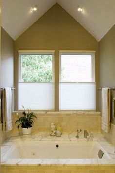 Cellular shades. Many bathrooms, especially those on the first floor, need maximum privacy. This bathroom has a hard window treatment called a cellular shade. Referred to as a top-down/bottom-up shade, this shade allows you to walk around without being seen and still lets a lot of light in.    Tip: It's constructed with a honeycomb design to keep the cold out and the heat in.