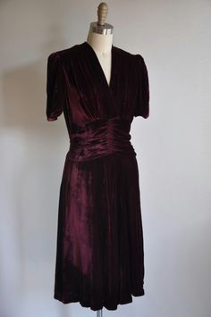 Early 1930s art deco velvet dress. V-cut in the front. Theater draping around the waist line. Gathered bust area. Small around edge shoulder pads. Velvet belt buckle in the back. Side metal zipper for closure.