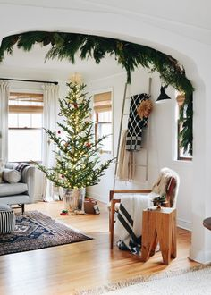 living room, christmas tree in metal can, white walls, garland on archway, wood table, blanket ladder, blue diamond quilt, white drapery, frasier fir