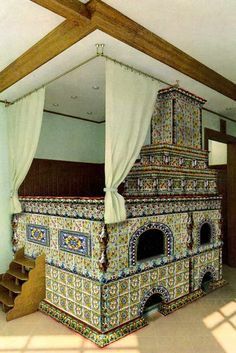 A spectacular example of a tile-covered Russian stove in the peasant style, with a space for sleeping on top, and steps to climb up