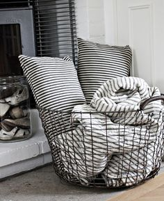 wire basket near the fireplace for blankets and pillows