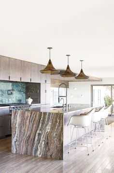 A trio of Mali pendants hangs above the kitchen island, which is wrapped in moonstone quartzite, and custom fiberglass barstools. Modern appliances include a stainless-steel cooktop from Bertazzoni, a faucet and pot filler by Dornbracht and integrated Sub-Zero refrigerator.