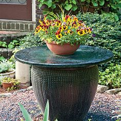 Pansies Large pots can be repurposed around your yard. This unused pot fountain was repurposed as an accent table and stand for a cheerful container planting.