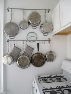 Hanging pots and pans is an effective way to clear out those kitchen cupboards and stop the clutter.