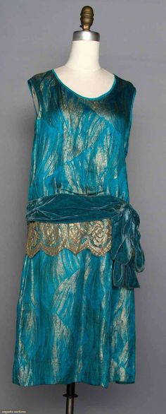 """TURQUOISE LAME DRESS, 1920s  Turquoise silk satin w/ gold frond brocade, sleeveless, velvet hip sash w/ gold lace, B 36"""", H 36"""", L 42"""", (2 large tarnish marks on back of dress, lace & possibly sash later additions) fair."""