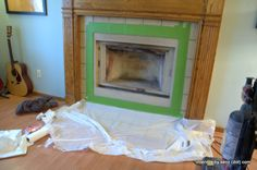 cheap and easy fireplace makeover _ rustoleum high heat ultra: spraying the box, painting the mantel, and putting beadboard over the tile! (remember though, beadboard is not up to code...)