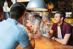 Happy Friends With Drinks Talking At Bar Or Pub Stock Photo - Image: 74690436